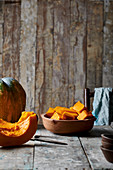 Pumpkin pieces in a ceramic bowl on a wooden table