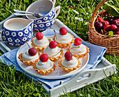 Frischkäse-Törtchen mit Kirschen auf Tablett im Freien