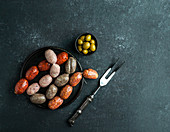 Spanish sausages on the cutting board - butifarra blanca, chorizo, morcilla de cebolla