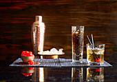Zwei Drinks, daneben Cocktailkirschen, Eiswürfel und Cocktailshaker