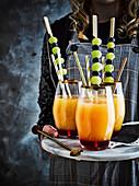 Frau serviert Mocktails mit Fruchtspießen