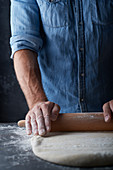 A man rolling out dough