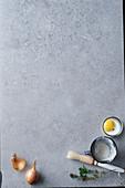Grauer Hintergrund mit Zwiebel, Mehl, Ei, Kräutern und Pinsel