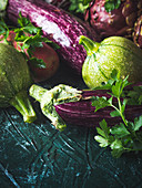 Purple and green vegetables - aubergines, red potatoes, chicory, artichokes and zucchini