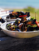 Mussels with chilli and herbs in bowls on an outdoor table