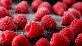 Fresh raspberries being dusted with icing sugar