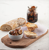 White bowl with preserved garlic and balsamic vinegar on wooden table with some slices of bread