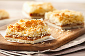 A slice of coconut cake filled with caramel on a wooden plate