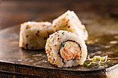 Sushi roll with salmon, cream cheese and green onion covered with sesame seeds