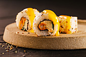 Sushi rolls filled with fried shrimp and cream cheese, covered with mango sauce.