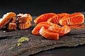Four pieces of sashimi on black stone plate