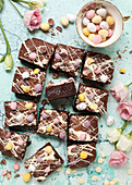 Chocolate brownies for Easter decorated with white chocolate and pastel coloured mini eggs