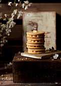 Stack of buttercream filled biscuits in a rustic setting