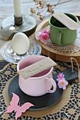 Namensschilder auf den Tassen auf romantisch gedecktem Tisch