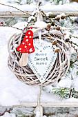 Kranz mit Fliegenpilz, Herz, Lärchenzapfen im Schnee