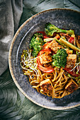 Fried vegetables with soba noodles, tempeh and a peanut and chilli sauce (vegan)