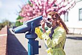 Woman using coin-operated binoculars