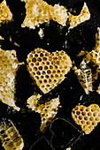 Honeycomb in heart shape on black background