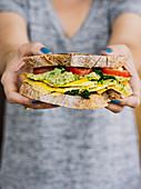 Woman holding omelette avocado sandwich