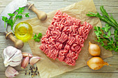 Raw minced meat with ingredients on a wooden surface