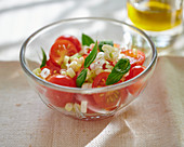 A tomato salad with spring onions and basil