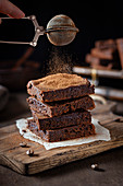 Brownies being dusted with cocoa