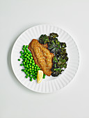 Fish schnitzel with kale chips and peas