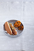 A hot dog with an algae sausage with sweet potato crisps