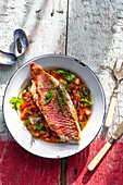 Fried red mullet fillet on a tomato and onion salad with fresh herbs