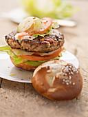 A lye bread burger with salad