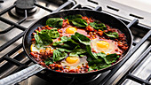 Shakshuka with spinach cooking in pan