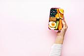 Frauenhand hält Lunchbox mit gesunden Snacks