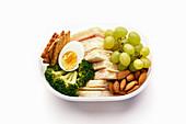 Lunchbox mit gesunder Mahlzeit aus Sandwich, Crackern, Obst, Gemüse, Ei und Mandeln