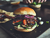 A grilled vegetable burger with vegan bacon
