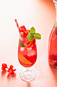 Summer iced punch with fresh raspberries, strawberries and peaches