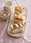 Choux pastry slices from the tray with whipped cream and caramel cream