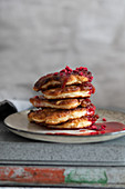 Stack of homemade fritters with raspberry coulis