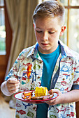 Boy eating sausage, sweet potato and sweetcorn bake
