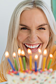 Woman smiling behind birthday candles