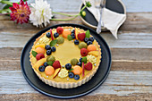Vegan tutti-frutti summer tart with peach and blueberry cream
