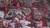 Brennende Holzkohle mit Eisenstange auf dem Grill verteilen