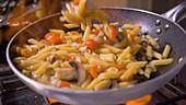 Nudeln mit Gemüse und Pilzen in der Pfanne zubereiten