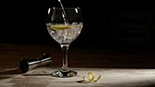 Person filling glass of gin tonic with lemon and jigger on table in dark room