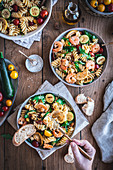 Mediterranean pasta salad with rocket, tomatoes and grilled prawns