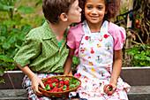 Zwei Kinder mit einem Korb Erdbeeren im Garten