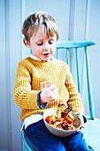 Junge isst Wursteintopf (Slow Cooking) mit Spiralnudeln
