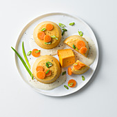 Carrot flans with spring onions and cheese sauce