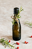 Black mini bottle of champagne decorated with rosemary
