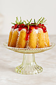 Vanilla bundt cake decorated with cranberry sauce and rosemary