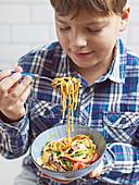 Boy eating noodle stir-fry with crunchy peanuts